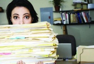 woman holding large stack of papers, hiring the right staff