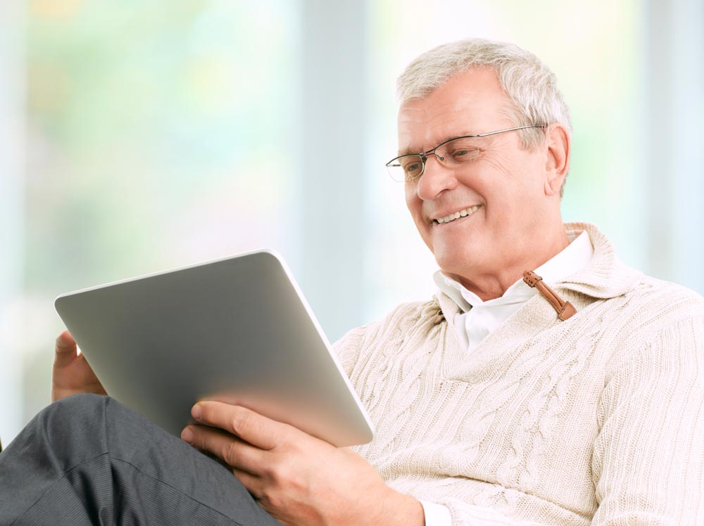 Retired man smiling at tablet