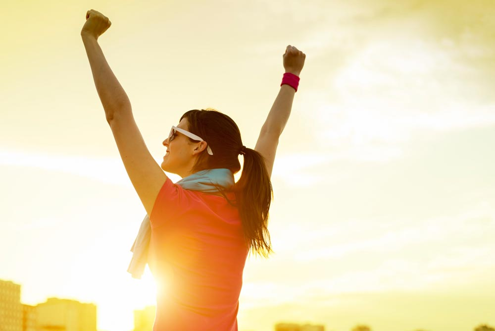 Woman with arms raised, energy supplements