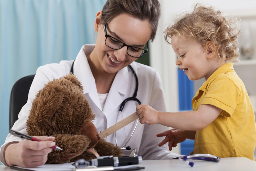 Doctor with child patient examining teddy bear
