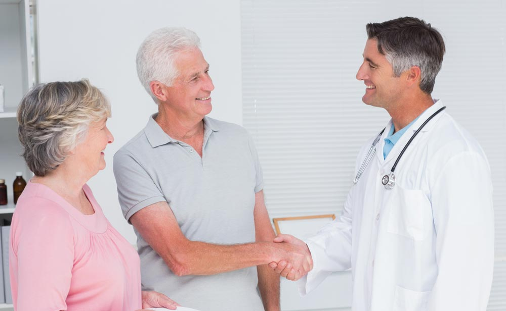 Doctor and couple agreeing on a treatment plan